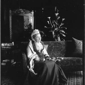 G36-033-05 Interior. Lacy with lace cap and black net mittens and shawl, seated with knitting on her lap. Arum lillies in the background.jpg