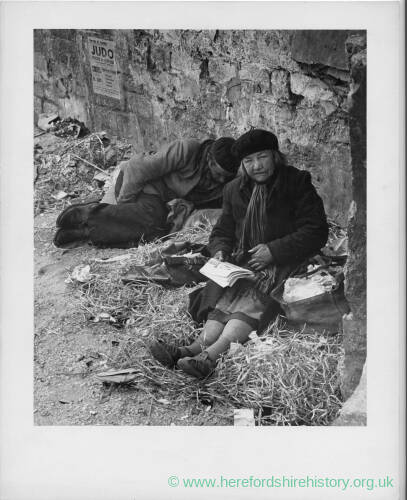 684 - Man and woman sitting on hay in front of wall