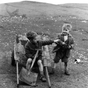 Two young boys. One sat in a wheelbarrow holding a large shovel.