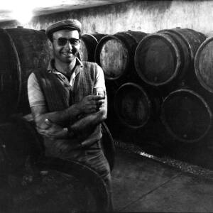 A workman posing in front of barrels of cider at H.P. Bulmer in Hereford.