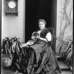 G36-033-01 Mrs Leigh holding a Pekinese dog, seated in doorway of Deanery .jpg