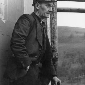422 - Coal Miner leaning on pole with cigarette