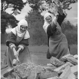 257-258 - Two nuns breaking stone with hammers
