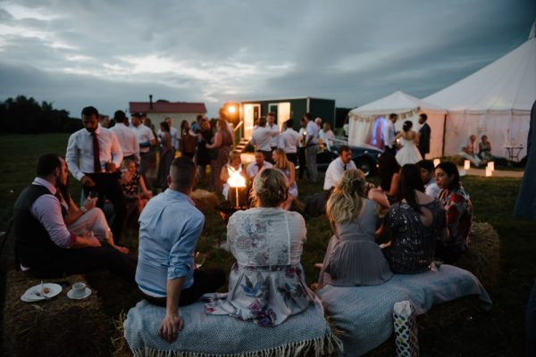 documentary photograph at a festival back garden wedding. Guests are sitting on hay bails around a fire and drinking