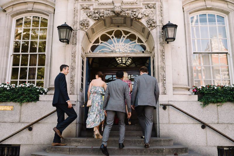 wedding guests entering Chelsea Town Hall in London. They are all wearing beautiful stylish outfits