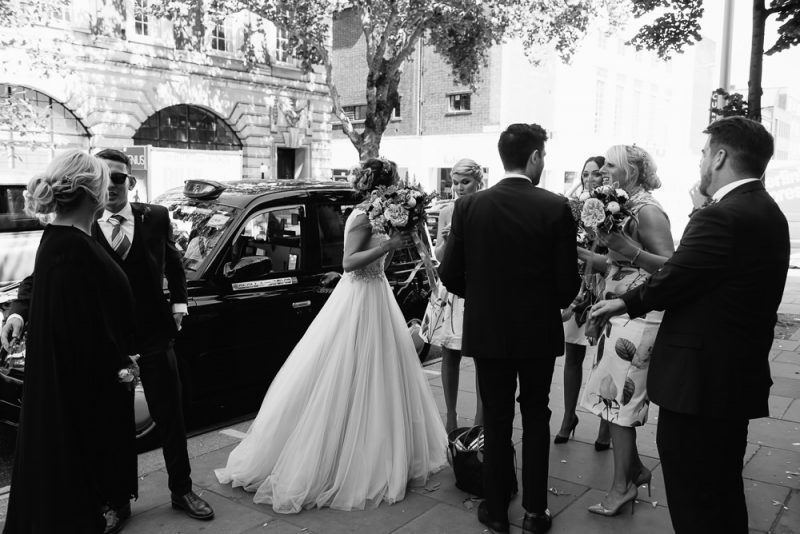 A bride, bridesmaids and her best gay friend are waiting to go into Chelsea Town Hall for a wedding