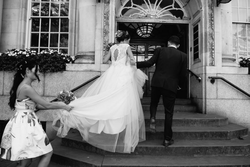 Bride and her brother walking up the stairs to Chelsea town hall