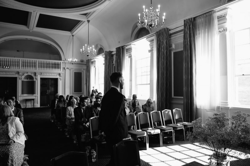 Groom waiting inside Chelsea town hall for their civil ceremony