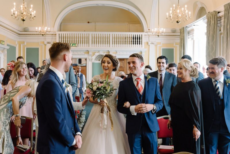 Bride is walked down the aisle by her brother, she is smiling widely as she see's her fiancé