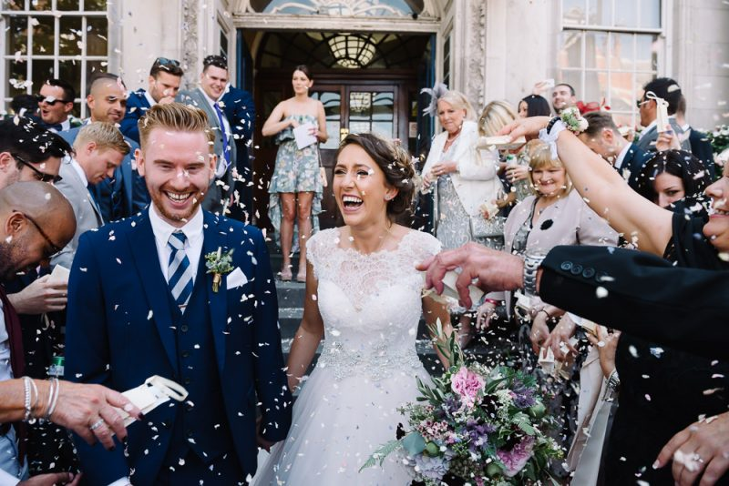 confetti is being thrown over a smiling couple just after their wedding