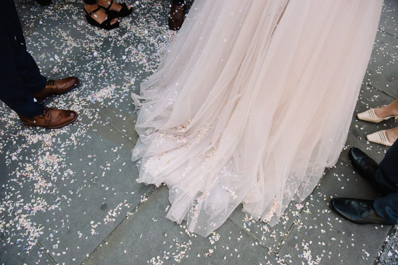 confetti is on the floor and the beautiful pink wedding dress of a bride