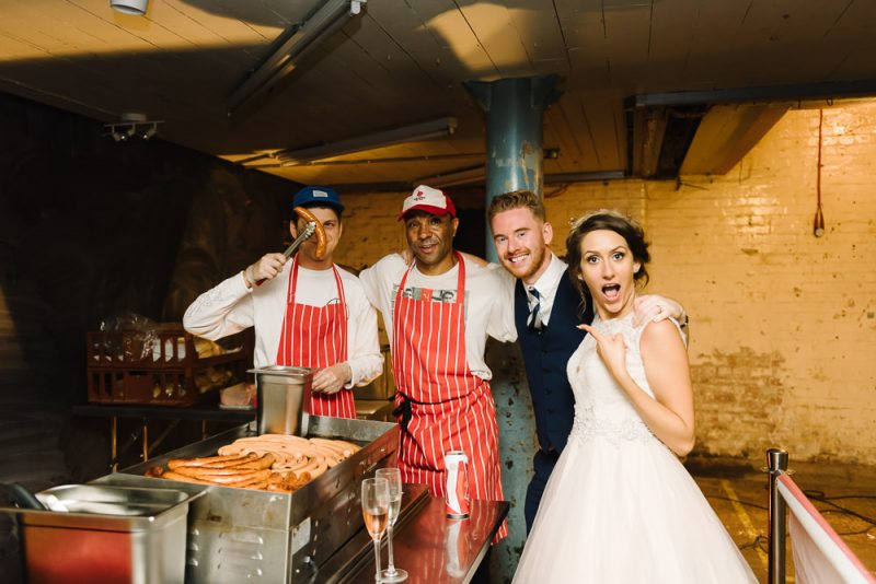 wedding couple posing in front of a hot dog stall