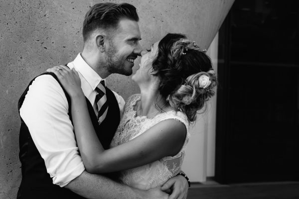 a documentary wedding photograph of a stylish couple, kissing on the Soutbank in London
