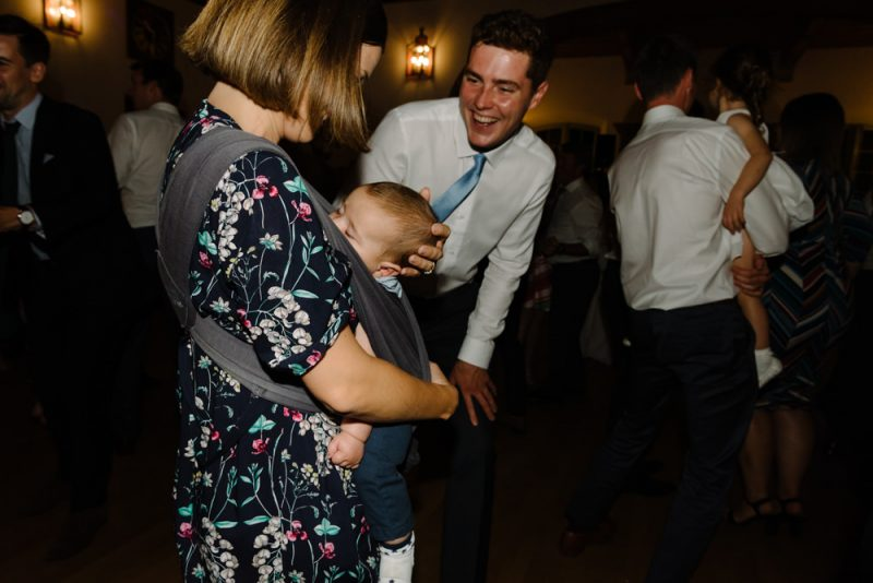 A baby is asleep in a sling being held by his mother at a wedding reception, a man is looking on a smiling