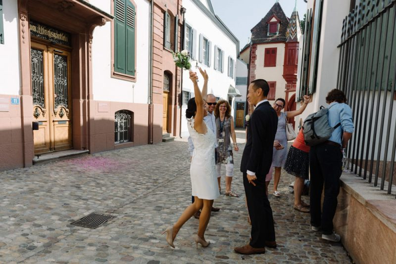 A bride is wearing a short stylish wedding dress and is throwing her hands in the air in joy, she is surrounded by friends and family at a Basel Wedding