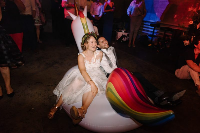 Bride and Groom sitting on a blow up Unicorn at their wedding