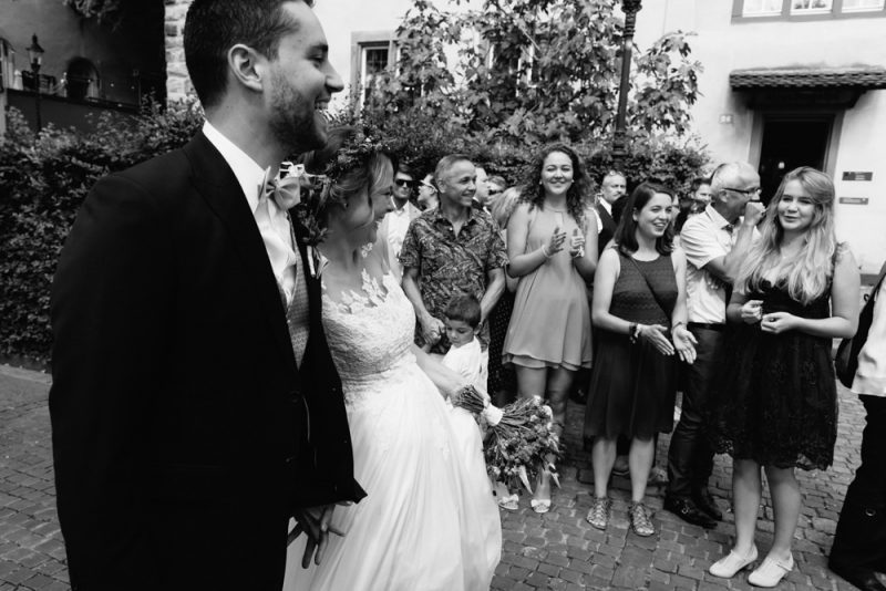Couple standing hugging each other in front of their friends and family who are looking on a smiling. She is wearing a flower crown. Ostquai, Basel wedding photography by Caroline Hancox Photography