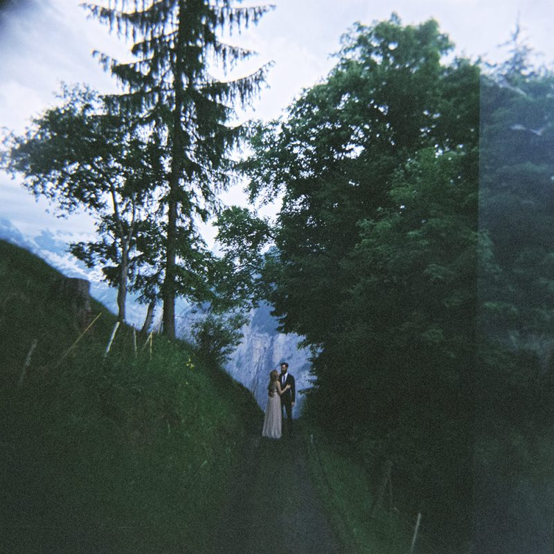 couple in the woods posing for a photograph on their elopement in Wengen looking out at the view taken on a Holga camera