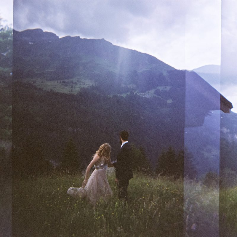 couple on a mountainside elopement looking out at the view taken on a Holga camera