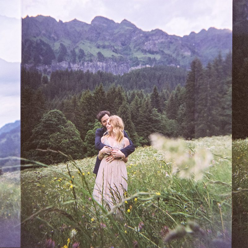 beautiful couple, she is wearing a pink wedding dress in the mountains in Switzerland just married, posing for a photograph