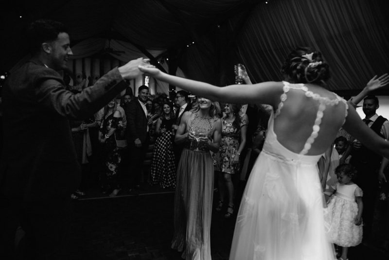 A couple are dancing at their wedding and their guests are watching and smiling, the wedding is at South Farm and was photographed by Caroline Hancox Photography