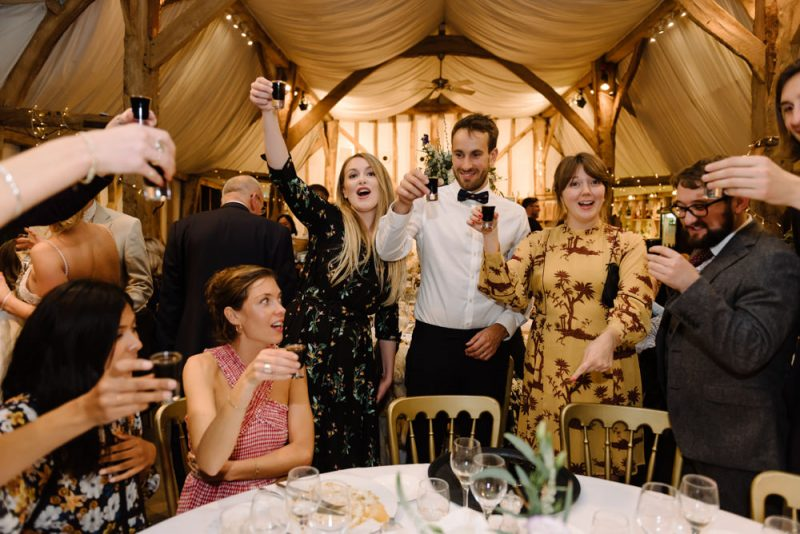 Guests doing shots at a wedding at South Farm by Caroline Hancox Photograhy