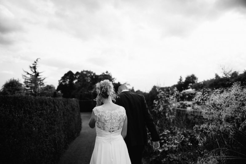 A couple are walking away from the camera holding hands there are bushes and grasses on each side of them