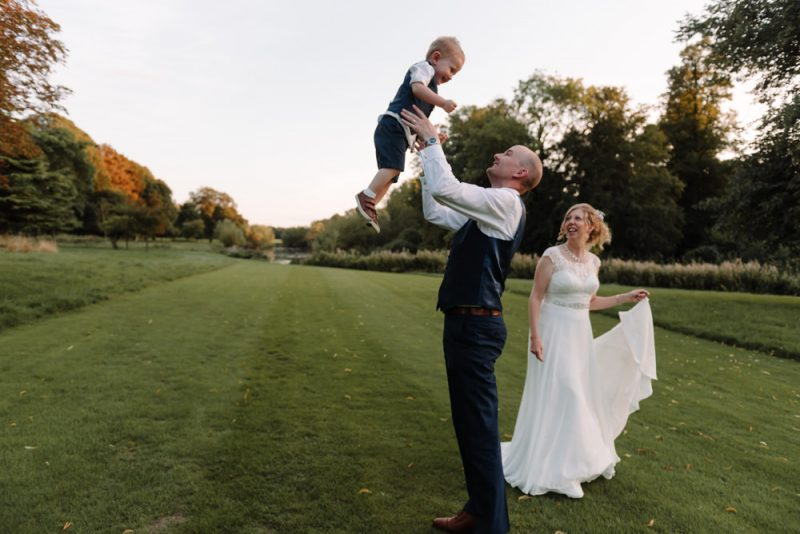 A Dad is throwing his little boy up in the air. He is dressed in a suit because it is his wedding. There is a bride walking next to them both and smiling