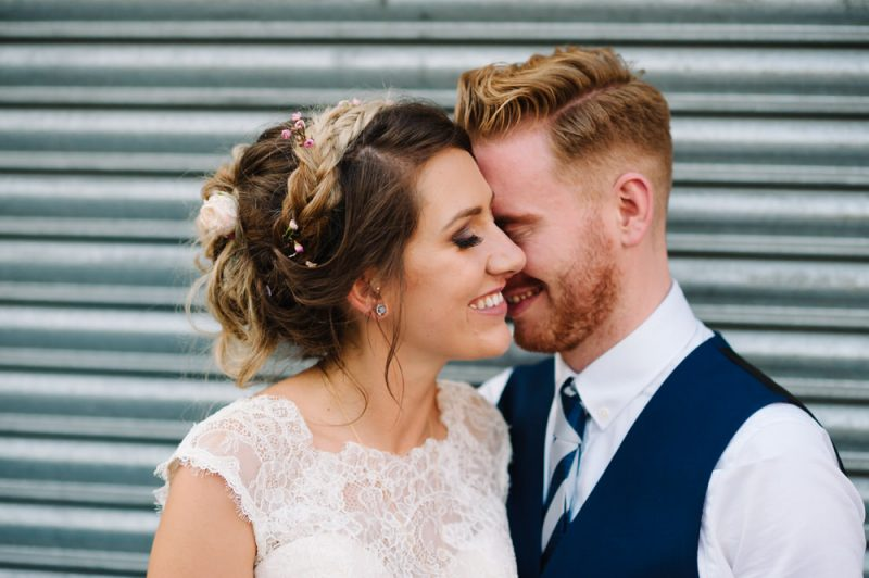 close up of a bride and groom on their wedding day i London, they are standing behind in front of a warehouse door