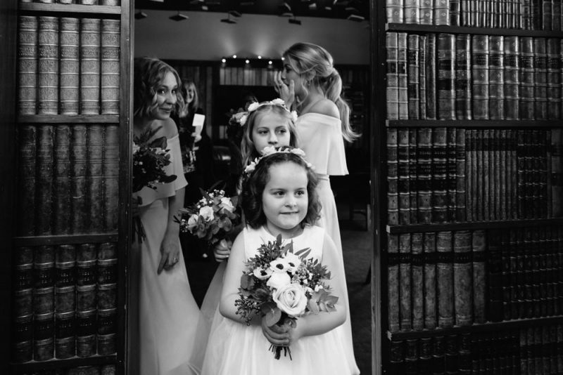 Some bridesmaids are peeking behind a bookcase waiting to all walk down the aisle