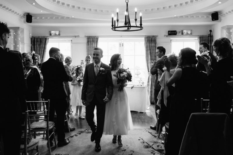 Couple walk back up the aisle after getting married they are both smiling to their guests