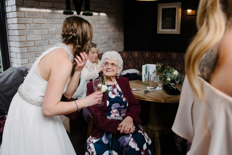 The wedding is in a pub and the bride is talking to her grandma, her grandma is very happy