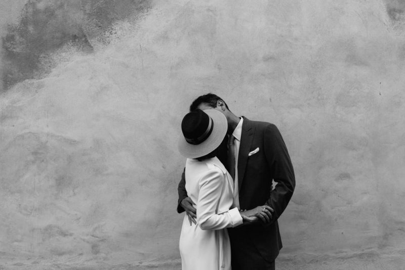 an older couple are kissing on their wedding day. She is wearing a stylish jumpsuit and a hat
