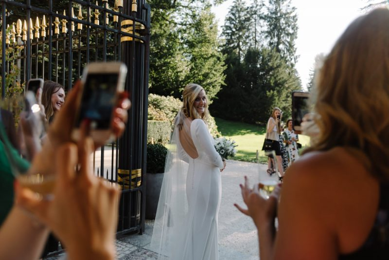 Beautiful bride is having her photo taken by her friends on their phones, she is smiling