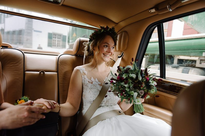 Bride is nervously waiting in an old Rolls Royce car from the Troi Rois in Basel, she is smiling but has tears in her yes and is wearing a flower crown.