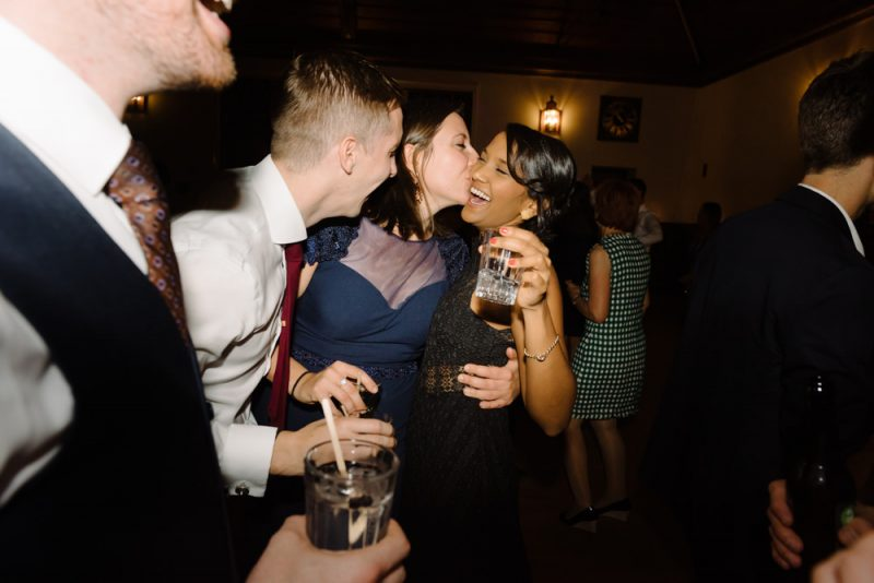 Friends hugging and kissing each other at a wedding reception.