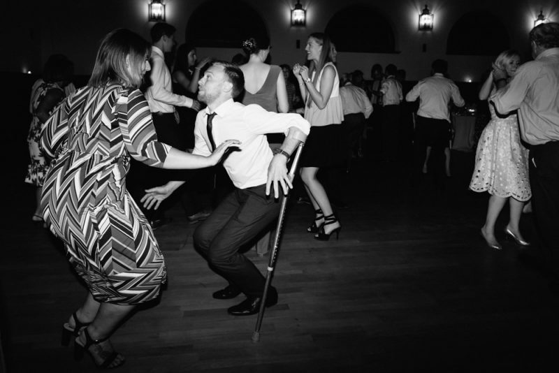 Man with a crutch dancing at a wedding at Villa Wenkenhof in Basel