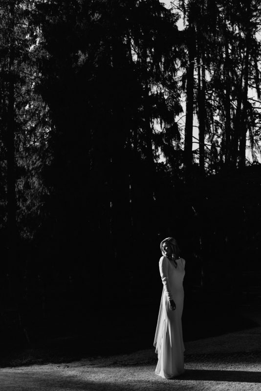 A bride is standing in a pol of bright light in amongst dark shadows and trees, she is wearing a long sleeved beautiful white gown