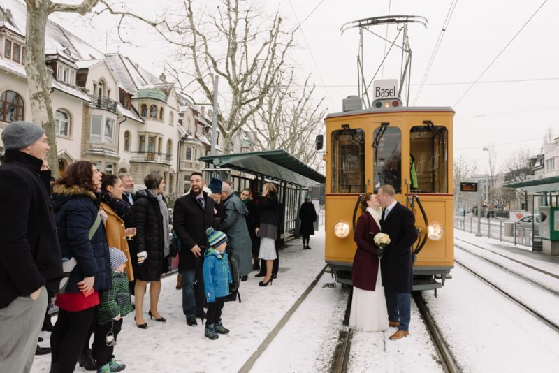Couple kiss in front of a yellow old-timer tram in the snow in Basel with friends and family smiling and cheering