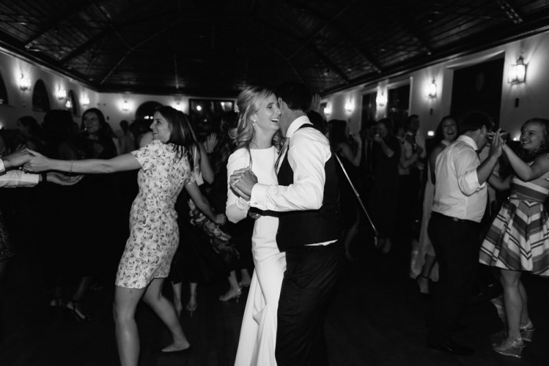 Bride and groom kissing as their first dance ends and their guests start to take to the dance floor.