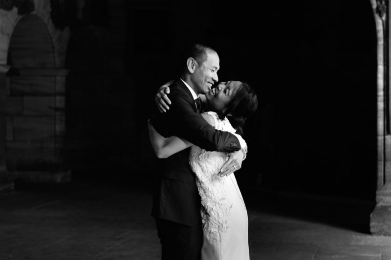 A bride and groom hugging and laughing after their wedding