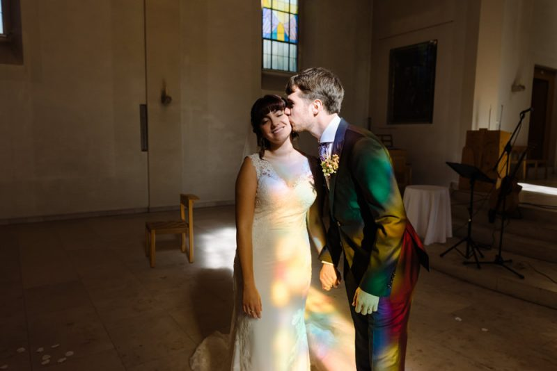 a groom is kissing his bride on the cheek and she is smiling. They are in a church and the colourful reflection from the stained glass is on them