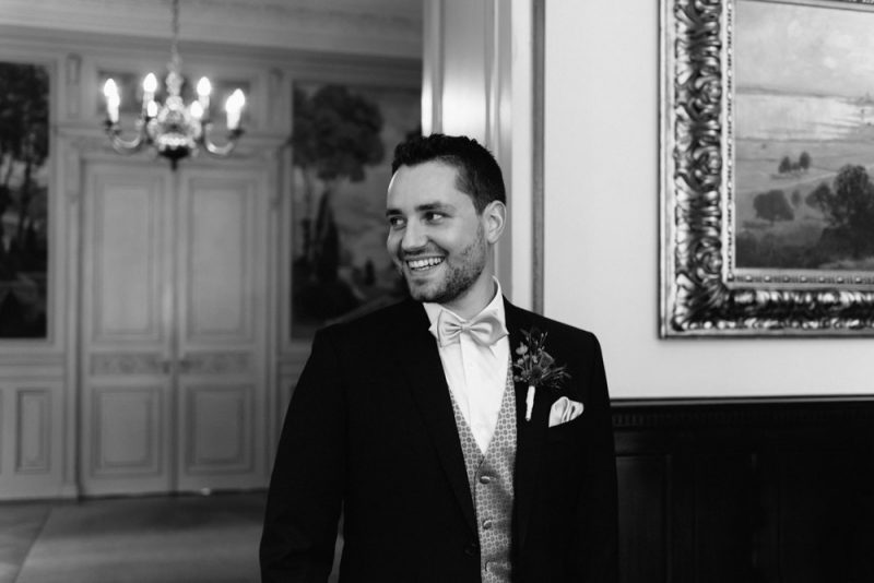 A handsome groom is looking it at his bride and smiling