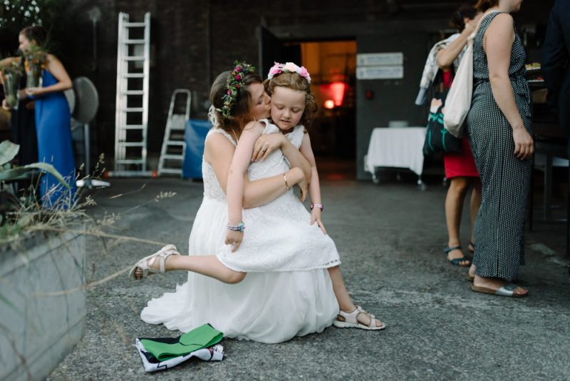 A bride is hugging and kissing a little girl on the check but the little girl looks like she wants to run away! Wedding photograph taken at Ostquai in Basel by Caroline Hancox