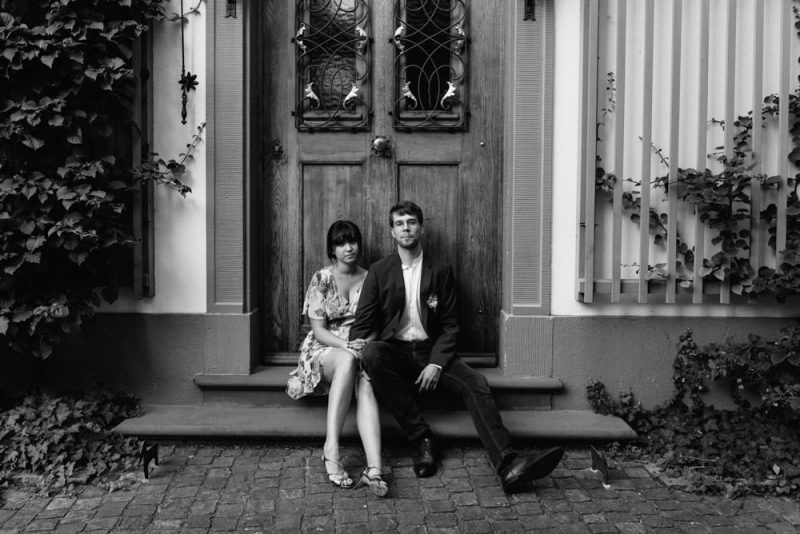 Couple sit on some steps in front of a big door, they are snuggled into each other but are looking at the camera
