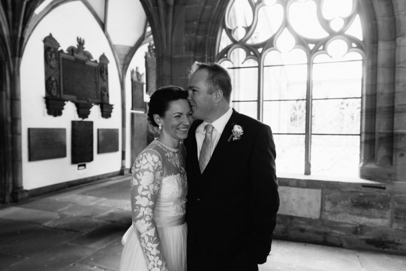 groom kisses his new wife on her head, they are both smiling. you can see cloisters of Basel Munster in the background