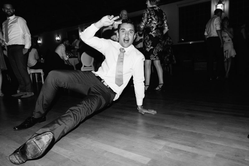 A man is posing on the dance floor on the floor and smiling