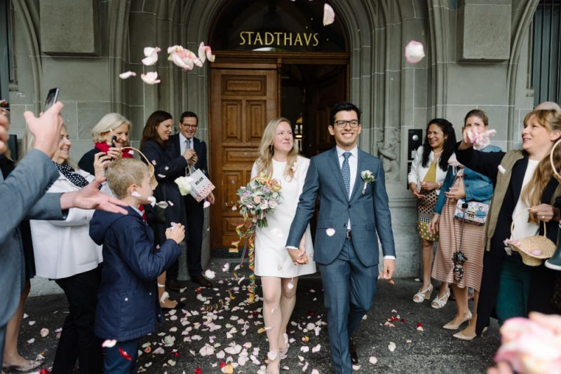 outside Zurich Stadthaus a couple walks out with confetti being thrown on them. Urban wedding photography by Caroline Hancox Photography