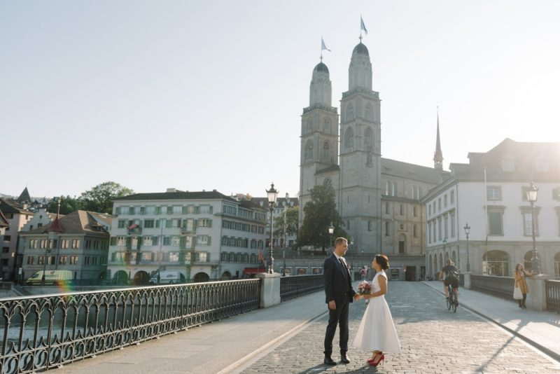 couple posing for a photo in front of the Grossmünster in Zurich on their wedding day