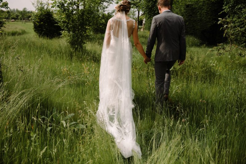 couple posing for their wedding photographs, they are walking away into a field and holding hands